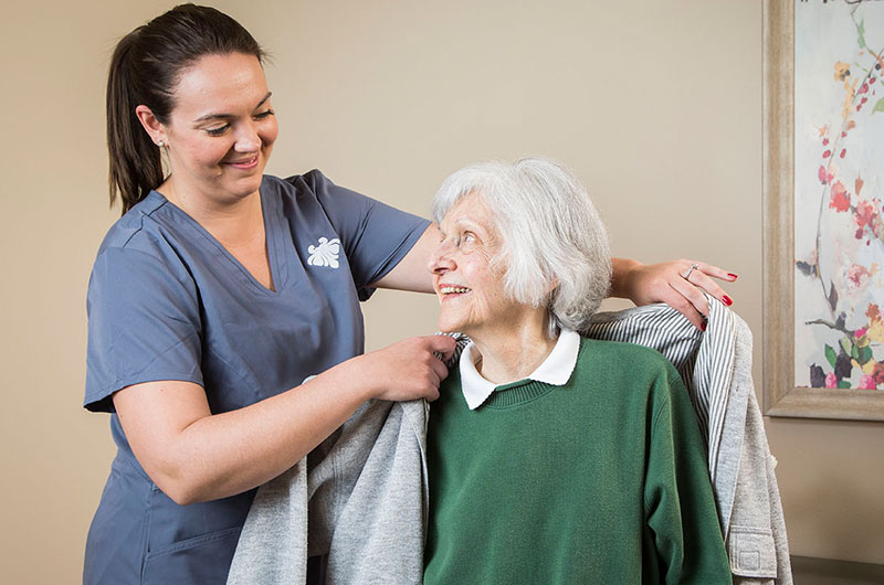 A-kind-nurse-assists-a-10-Wilmington-Place-resident-in-wearing-their-coat (1)