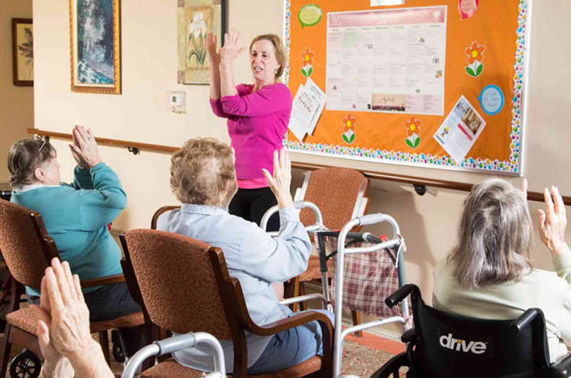 10 wilmington place residents actively participating in a chair yoga class following a passionate instructor