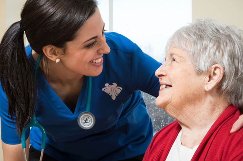 skilled nurse smiles at a resident who smiles back