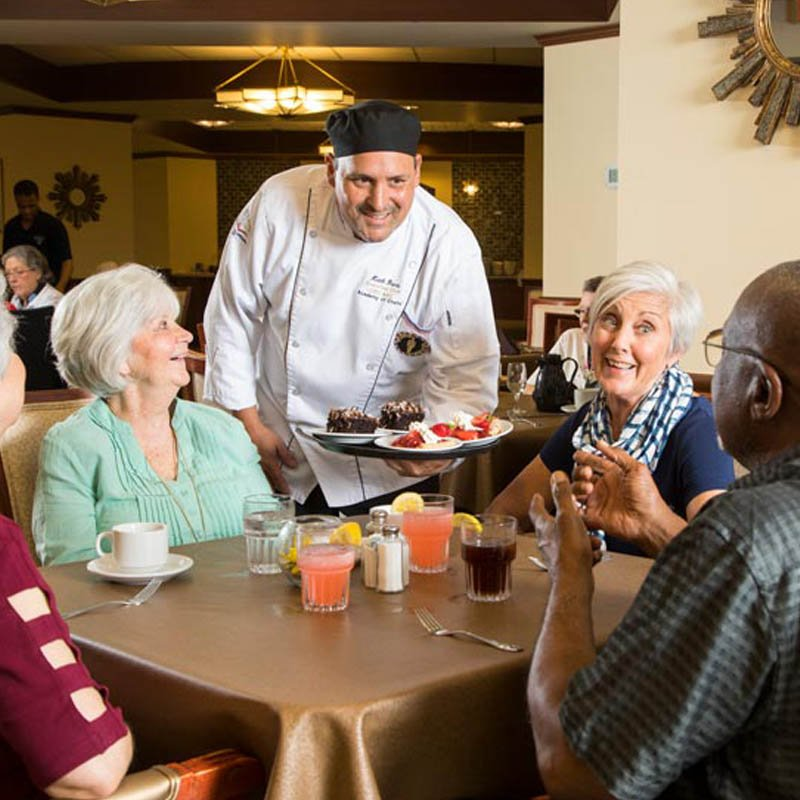 the chef at 10 wilmington place offering dessert to a group of residents in the dining area