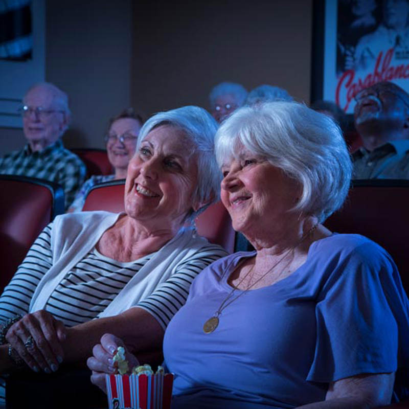 two senior ladies enjoying a movie in the cinema